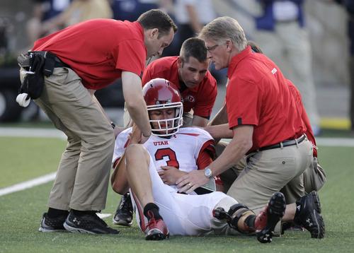 Utah quarterback Jordan Wynn (3) is helped off the field following a hit during the second quarter of an NCAA football game against Utah State on Thursday, Sept. 7, 2012, in Logan, Utah. (AP Photo/Rick Bowmer)