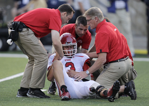 Utah quarterback Jordan Wynn (3) is helped off the field following a hit during the second quarter of an NCCA football game against Utah State on Thursday, Sept. 7, 2012, in Logan, Utah. (AP Photo/Rick Bowmer)