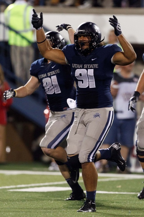 Trent Nelson  |  The Salt Lake Tribune Utah State's D.J. Tialavea celebrates a touchdown in the second half as Utah State hosts the University of Utah, college football in Logan, Utah, Friday, September 7, 2012.