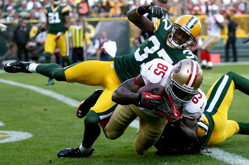San Francisco 49ers tight end Vernon Davis (85) hauls in a touchdown pass while being defended by Green Bay Packers cornerback Sam Shields (37) in the second quarter of an NFL football game, Sunday, Sept. 9, 2012, in Green Bay, Wis. The 49ers won 30-22. (AP Photo/Shawano Leader, Cory Dellenbach)