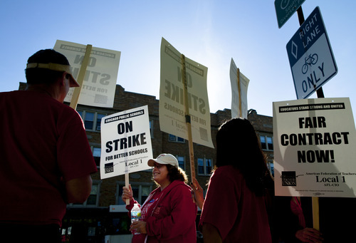 Sitthixay Ditthavong  |  The Associated Press Public school teachers picket outside Amundsen High School in Chicago on the first day of a strike by the Chicago Teachers Union, Monday, Sept. 10, 2012. The school is one of more than 140 schools in the Chicago Public Schools'