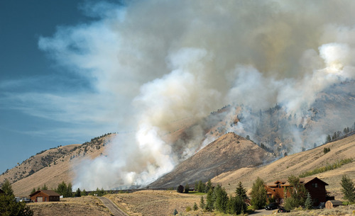 In this Saturday, Sept. 8, 2012 photo, a wildfire spreads through Wilson Canyon, as seen from Little Horsethief Lane, south of Jackson, Wyo. Trails, lifts and other mountain operations at Snow King Resort are closed due to the fire, which is burning less than 3 miles south of the town hill. (AP Photo/Jackson Hole News & Guide, Price Chambers)