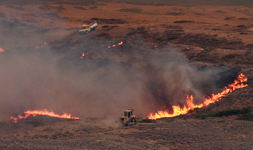 A bulldozer helps build a fire line as flames from the Casper Mountain wildfire spread into the grassy foothills at the eastern base of the mountain Monday, Sept. 10, 2012 in Casper, Wyo. The fire spread rapidly eastward Monday morning and had burned about 10,000 acres by 1 p.m. (AP Photo/Star-Tribune, Alan Rogers)