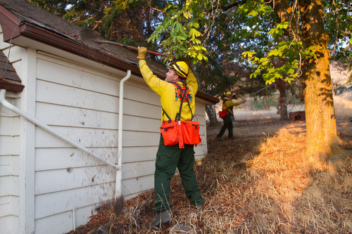 A Snohomish County fire crew attempts to clear brush and debris away from a vacant house in Wenatchee, Wash., about 140 miles east of Seattle, Tuesday morning, Sept. 11, 2012, as a brush fire approaches. About 180 homes in Wenatchee were evacuated Sunday, Sept. 9. Some residents were allowed to return, while others were told to leave Monday, a police spokesman said. (AP Photo/The Wenatchee World, Don Seabrook)