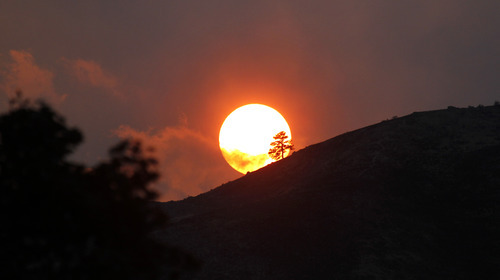 The sun and nearby clouds of smoke turn a brilliant red where a wildfire burns  Monday evening, Sept. 10, 2012, near Wenatchee, Wash. Crews in central Washington and Wyoming worked Monday to protect homes from two of the many wildfires burning throughout the West as a destructive fire season stretches into September with no relief expected from the weather anytime soon.  (AP Photo/Elaine Thompson)