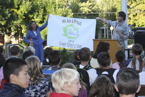 Cynthia Norton and Josh Wennergren unfold the Utah Green Schools Flag for Bonneville Elementary. On Friday, September 7, 2012, the school won the Platinum Utah Green Schools Award for their green efforts during the 2011-2012 school year. Photo courtesy Bonneville Elementary.