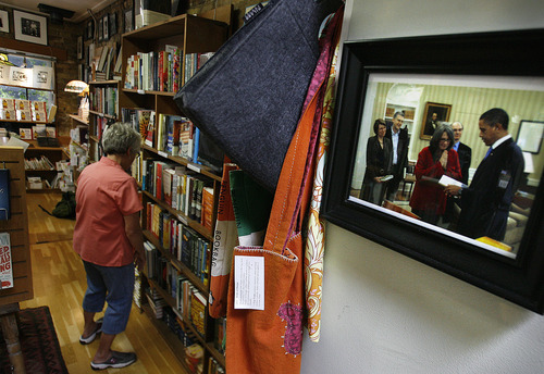 Scott Sommerdorf  |  The Salt Lake Tribune              A photo made in 2010 shows owner Betsy Burton presenting President Obama framed book hangs at The King's English Bookshop.