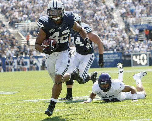 Chris Detrick  |  The Salt Lake Tribune Brigham Young Cougars running back Michael Alisa (42) runs for a touchdown past Weber State Wildcats linebacker Roman Valenzuela (50) during the first half of the game against Weber State at LaVell Edwards Stadium Saturday September 8, 2012. BYU is winning the game 21-0.