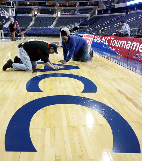 FILE - This March 9, 2005 file photo shows Kim Webster, left, and Phil Westmoreland placing the ACC logo on the floor of the MCI Center in Washington prior to the start of the Atlantic Coast Conference basketball tournament. Notre Dame is leaving the Big East for the Atlantic Coast Conference in all sports but football. The ACC said Wednesday, Sept. 12, 2012, the school will play five football games annually against the league's programs, but will be a full member in all other sports.  (AP Photo/Lawrence Jackson, File)