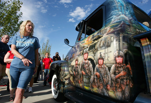 Steve Griffin | The Salt Lake Tribune   Julie Vinnedge, mother of Lance Corporal Phillip David Vinnedge, who died while serving in Afghanistan, gives people a tour of a vintage truck his parents restored in his honor during an event at  In his honor, at Fairbourne Station Plaza, in West Valley City, Utah Tuesday September 11, 2012. His parents fulfilled his dream of restoring a 1951 Chevy truck complete with murals honoring him, his family, his military colleagues and those lost on September 11, 2001. Lance Cpl. Vinnedge's parents now travel and display the truck in memory of their son. They will be in Camp Pendleton Sept. 13, 2012 to show the truck to his son's platoon. Phillip was deployed with the 3rd Battalion, 5th Marine Regiment to Afghanistan and on October 13, 2010 Phillip was driving the lead vehicle on a security patrol with Lcpl Victor Dew, Lcpl Joe Rodewald and Cpl Justin Cain when a large IED was remotely detonated killing all 4 instantly. The four soldiers are painted on the driver side door pictured here.