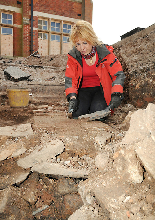 Undated University of Leicester handout photo of Karen Ladniuk, from the Richard III society, cleaning a path made from re-used medieval tiles during an excavation of the car park behind council offices in Leicester, made available Wednesday Sept. 12, 2012. Archaeologists searching under the city center car park for the lost grave of Britain's King Richard III have discovered human remains. Bones unearthed during the dig have been sent for DNA testing and the experts hope that they turn out to be those of the medieval king. Contemporary chronicles say Richard's body was brought to Leicester, 100 miles (160 kms) north of London, after the king was killed in the Battle of Bosworth Field in 1485.(AP Photo/ University of Leicester)