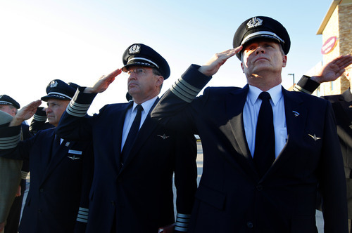 Airline pilots Capt. Anthony Chapman, right, and  Capt.  Paul Evans salute with others as  the U.S. flag is lowered to half staff at the 9/11 Flight Crew Memorial in Grapevine, Texas, Tuesday, Sept. 11, 2012.  Flight crews gathered at the memorial near DFW airport to remember the flight crews lost in the  Sept. 11, 2001, terror attacks.  (AP Photo/LM Otero)