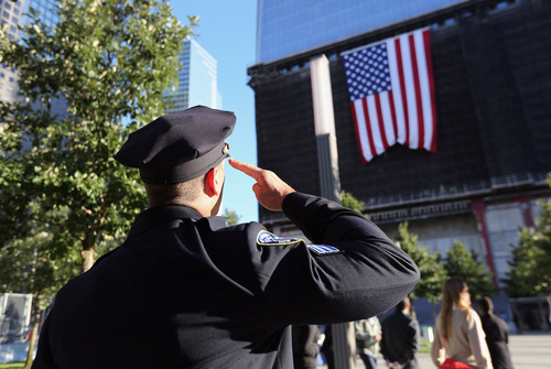 A New York City Police officer salutes a flag hanging from the One World Trade Center building, during ceremonies for the 11th anniversary of the attacks at the World Trade Center, in New York, Tuesday Sept. 11, 2012. (AP Photo/John Moore, Pool, Getty Images)