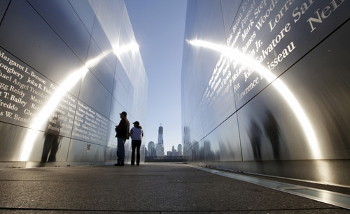 The construction of One World Trade Center, now up to 104 floors, is seen Tuesday, Sept. 11, 2012, across the Hudson River, as people stop to read names in New Jersey's memorial to the 749 people from the state lost during the  Sept. 11 terrorist attacks on the World Trade Center.  Americans paused again Tuesday to mark the 11th anniversary of the Sept. 11, 2001, terror attacks with familiar ceremonies, but also a sense that it's time to move forward after a decade of remembrance. (AP Photo/Mel Evans)