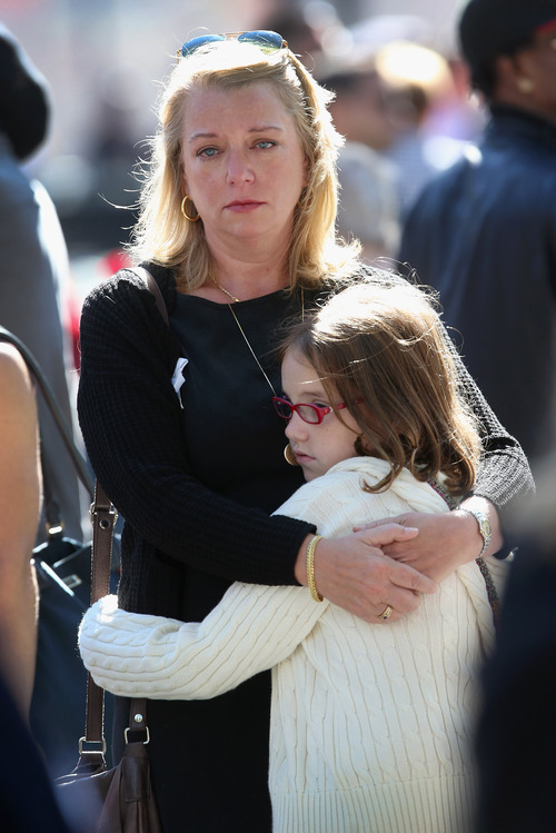 Nina Fisher, sister of 9/11 victim Andrew Fisher, embraces her niece Mia Tinson, 9, at a ceremony marking the 11th anniversary of the terrorist attacks on the World Trade Center, Tuesday, Sept. 11, 2012 in New York. (AP Photo/John Moore, Pool)