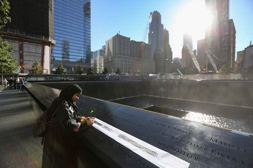 Khudeza Begum traces the name of her slain nephew on the 11th anniversary of the terrorist attacks on the World Trade Center, Tuesday, Sept. 11, 2012 in New York. Begum, who is from Bangladesh, lost her nephew, Nural Miah, and his wife, Shakila Yasmin, two of the many Muslims who died in the attacks on Sept. 11, 2001. (AP Photo/John Moore, Pool)