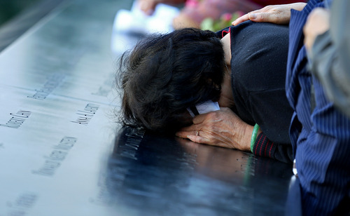A woman mourns on the wall engraved with the names of victims during observances on the eleventh anniversary of the attacks on the World Trade Center at the National September 11 Memorial in New York on September 11, 2012. (AP Photo/Craig Ruttle, Newsday, Pool)