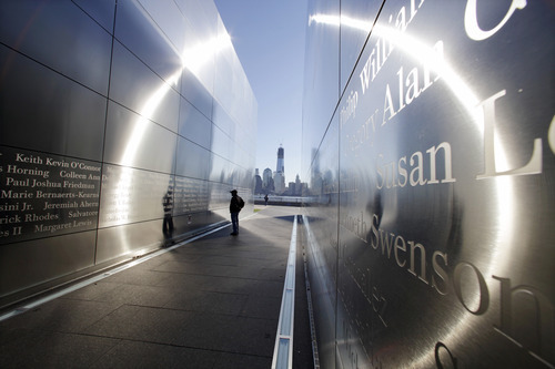 A person stops to read names in New Jersey's memorial to the 749 people from the state lost during the  Sept. 11 terrorist attacks on the World Trade Center, as One World Trade Center, now up to 104 floors, looms in the distance across the Hudson River, Tuesday, Sept. 11, 2012 in Jersey City, N.J.  Americans paused again Tuesday to mark the 11th anniversary of the Sept. 11, 2001, terror attacks with familiar ceremonies, but also a sense that it's time to move forward after a decade of remembrance. (AP Photo/Mel Evans)