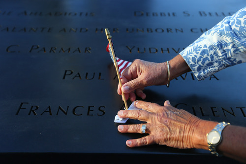 Judy Parisio places a small U.S. flag on the engraved name of her niece, Frances Ann Cilente who worked and died at the World Trade Center, during the commemoration ceremony of the 11th anniversary of the Sept. 11, 2001 terrorist attacks by the North Pool at World Trade Center in New York on Tuesday, Sept. 11, 2012. (AP Photo/The New York Times, Chang W. Lee, Pool)