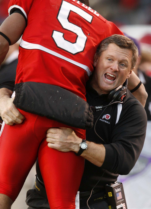 Utah coach Kyle Whittingham holds up wide receiver Brent Casteel (5) after Casteel's touchdown in the final minutes of the game. At the time, it looked like victory for Utah was inevitable. Salt Lake City - Utah vs. BYU college football at Rice-Eccles Stadium. Photo by Trent Nelson; 11.25.2006