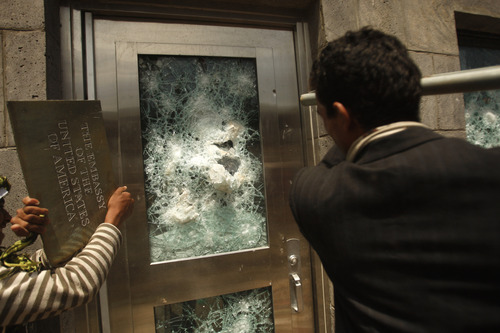 Yemeni protestors break a door of the U.S. Embassy during a protest about a film ridiculing Islam's Prophet Muhammad, in Sanaa, Yemen, Thursday, Sept. 13, 2012. Dozens of protesters gather in front of the US Embassy in Sanaa to protest against the American film