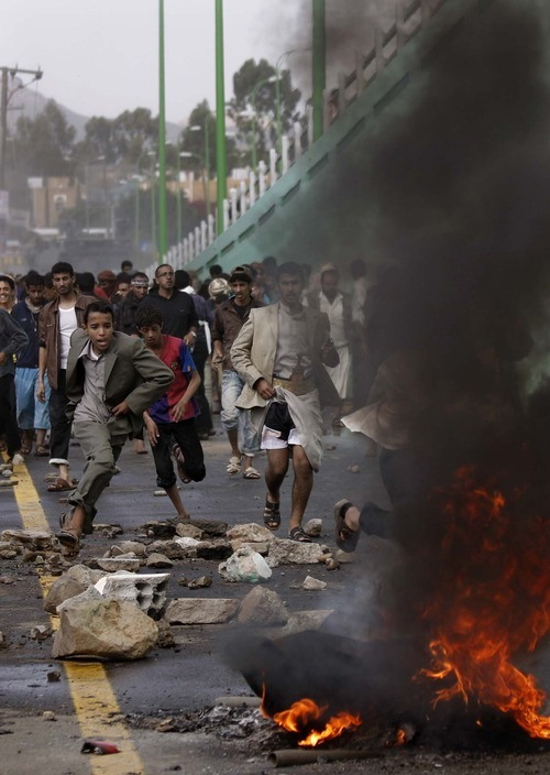 Protesters run as police open fire into the air near the U.S. Embassy during a demonstration about a film ridiculing Islam's Prophet Muhammad, in Sanaa, Yemen, Thursday, Sept. 13, 2012. Yemen's president has apologized to President Barack Obama for the attack on the U.S. Embassy in Sanaa, the Yemeni capital, by a mob angry over an anti-Islam film. (AP Photo/Hani Mohammed)
