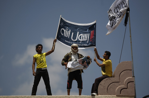 A Yemeni protester, center, destroys an American flag pulled down as other hold a banner in Arabic that reads,