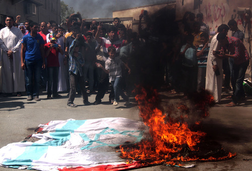 Bahrainis burn replicas of American and Israeli flags during a protest after midday prayers in Diraz, Bahrain, Friday, Sept. 14, 2012, as part of widespread anger across the Muslim world about a film ridiculing Islam's Prophet Muhammad. (AP Photo/Hasan Jamali)