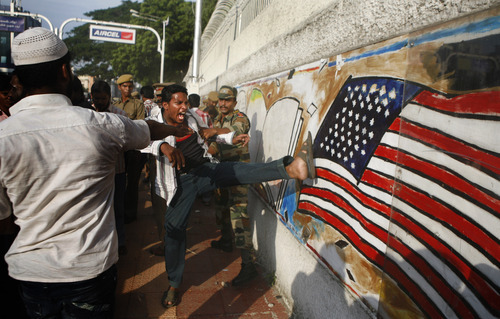 An Indian protester kicks at a graffiti of the American flag on a wall of the U.S. Consulate  during a protest against the anti-Islam film which depicts the Prophet Muhammad as a fraud, a womanizer and a madman in Chennai, India, Friday, Sept. 14, 2012.  (AP Photo/Arun Shanker K.)
