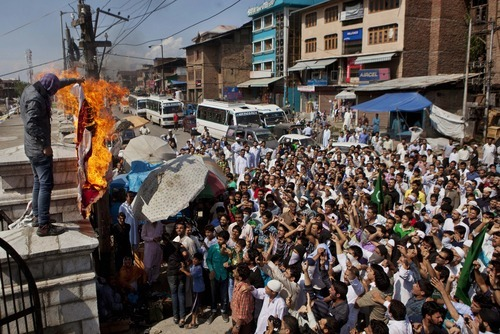 A Kashmiri Muslim with his face covered burns a mock American flag as others shout slogans during a protest in Srinagar, India, Friday, Sept. 14, 2012. The protest was held against an anti-Islam film called