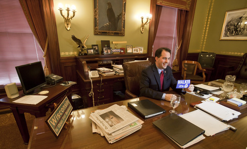 Wisconsin Gov. Scott Walker shows off a bumper sticker in his office during an interview at the state Capitol in Madison, Wis., Thursday, March 3, 2011. Opponents to the governor's bill to eliminate collective bargaining rights for many state workers is in it's 16th day at the Capitol. (AP Photo/Andy Manis)