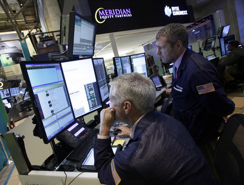 In this Thursday, Sept. 13, 2012 photo, a pair of traders work in their booth on the floor of the New York Stock Exchange, in New York.  Economic data is coming out of Washington on Friday on inflation, retail sales, industrial production and business inventories. (AP Photo/Richard Drew)