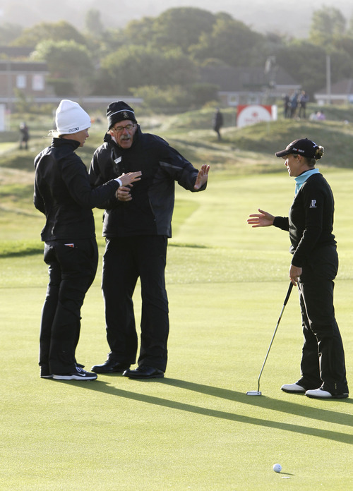 Peter Byrne   The Associated Press Suzann Pettersen, left, and Christie Kerr, right, talk to a rules official about the suspension of play because of high winds during day two of the Women's British Open.