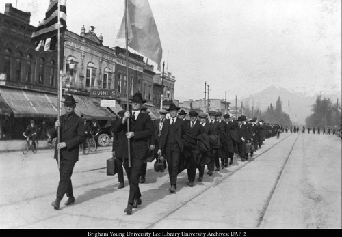With the revival of football in 1920 came also renewed enthusiasm. Followed by the student body, the football team marched down University Avenue to board a train for a game at Logan. Courtesy of BYU