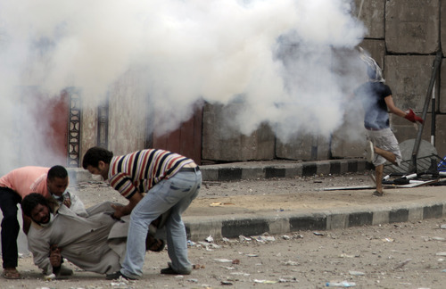 Egyptian protesters assist an injured comrade during clashes with security forces, unseen, near the U.S. embassy in Cairo, Egypt, Friday, Sept. 14, 2012, as part of widespread anger across the Muslim world about a film ridiculing Islam's Prophet Muhammad. (AP Photo/Khalil Hamra)