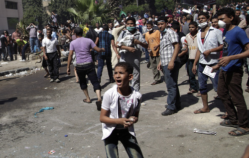 An Egyptian youth protester reacts during clashes with security forces, unseen, near the U.S. embassy in Cairo, Egypt, Friday, Sept. 14, 2012, as part of widespread anger across the Muslim world about a film ridiculing Islam's Prophet Muhammad. (AP Photo/Khalil Hamra)