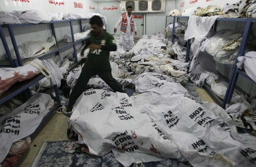 A Pakistani volunteer stands in a morgue where workers were killed in a factory fire, at a morgue in Karachi, Pakistan, Thursday, Sept. 13, 2012. Pakistani police say they have registered a murder case against the owners and managers of a garment factory in the southern city of Karachi where a fire killed hundreds of people. (AP Photo/Fareed Khan)