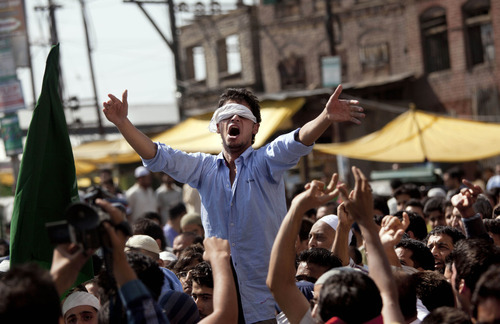 A Kashmiri Muslim man wearing blindfold shouts slogans during a protest in Srinagar, India, Friday, Sept. 14, 2012. The protest was held against an anti-Islam film called