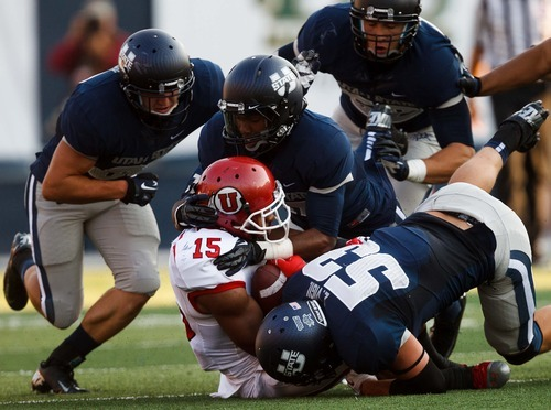 Trent Nelson  |  The Salt Lake Tribune Utah State defenders tackle Utah's John White during the first quarter as Utah State hosts the University of Utah, college football in Logan, Utah, Friday, September 7, 2012.