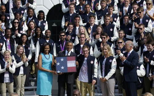 President Barack Obama, and first lady Michelle Obama are presented with the U.S. Olympic flag by Navy Veteran Brad Snyder, and Mariel Zagunis, during a ceremony welcoming the 2012 U.S. Olympic and Paralympic teams, Friday, Sept. 14, 2012, on the South Lawn of the White House in Washington. At far right is Vice President Joe Biden. (AP Photo/Pablo Martinez Monsivais)