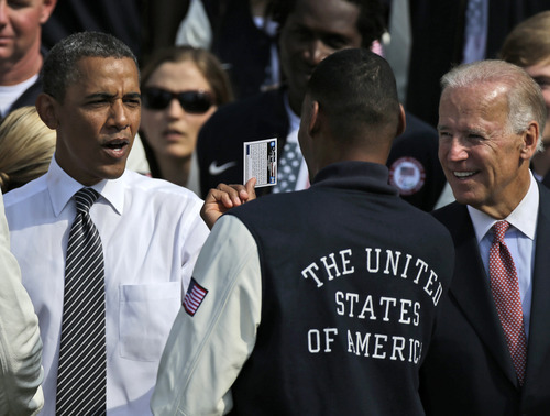 An unidentified member of the US Olympic team flashes a Barack Obama Campaign 2008 trading card to President Barack Obama and Vice President Joe Biden during a ceremony on the South Lawn of the White House in Washington, Friday, Sept. 14, 2012, where the president welcomed the 2012 U.S. Olympic and Paralympic teams. (AP Photo/Pablo Martinez Monsivais)