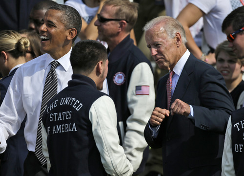 Vice President Joe Biden, accompanied by President Barack Obama,  jokes around with US Olympic boxer Jose Ramirez, on the South Lawn of the White House in Washington, Friday, Sept. 14, 2012, during a ceremony to welcome the 2012 U.S. Olympic and Paralympic teams. (AP Photo/Pablo Martinez Monsivais)