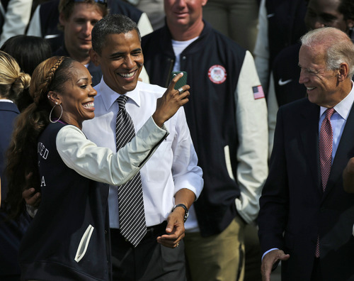 US Olympic team relay runner Sanya Richards-Ross uses her cell phone to take a photo with President Barack Obama, as Vice President Joe Biden watches at right, during a ceremony on the South Lawn of the White House in Washington, Friday, Sept. 14, 2012, where the president welcomed the 2012 U.S. Olympic and Paralympic teams. (AP Photo/Pablo Martinez Monsivais)