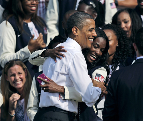 President Barack Obama is hugged by DeeDee Trotter, a member of the US Olympics relay team during a ceremony on the South Lawn of the White House in Washington, Friday, Sept. 14, 2012, where President Barack Obama welcomed the 2012 U.S. Olympic and Paralympic teams. (AP Photo/Pablo Martinez Monsivais)