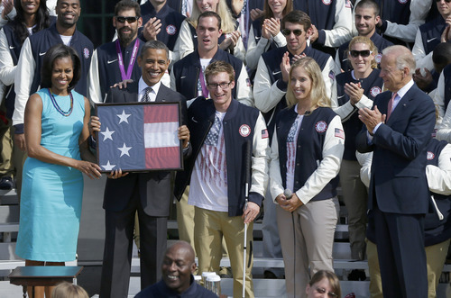From left, first lady Michelle Obama, President Barack Obama, U.S. Paralympic flag bearer and Navy Veteran Brad Snyder, U.S. Olympic flag bearer Mariel Zagunis, and Vice President Joe Biden, take part in a ceremony on the South Lawn of the White House in Washington, Friday, Sept. 14, 2012, to welcome the 2012 U.S. Olympic and Paralympic teams. President Obama was presented with the flag carried by Zagunis and Snyder during the Olympics. (AP Photo/Pablo Martinez Monsivais)