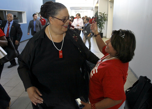Karen Lewis, president of the Chicago teachers union, left, is greeted by a union member after her meeting with the union's House of Delegates Friday, Sept. 14, 2012, in Chicago. Lewis told the delegates that a