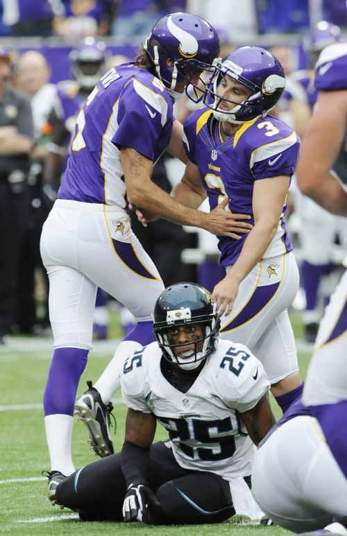 Jacksonville Jaguars strong safety Dwight Lowery (25) sits on the field as Minnesota Vikings punter Chris Kluwe (5), left, congratulates kicker Blair Walsh (3) on his go-ahead field goal during overtime in an NFL football game on Sunday, Sept. 9, 2012, in Minneapolis. The Vikings won 26-23. (AP Photo/Jim Mone)