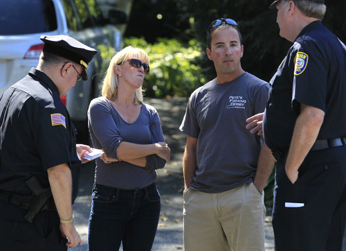 Kate Quigley, center left, who says her brother Glen Doherty was among the Americans killed in an attack on the U.S. Consulate in Libya, and her husband  Mark Quigley, center right, speak with Woburn, Mass., police, in Worburn, Thursday, Sept. 13, 2012. Four Americans were killed at the U.S. Consulate in Benghazi on Tuesday along with U.S. Ambassador Chris Stevens. (AP Photo/Steven Senne)