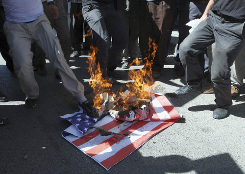 A mock U. S. flag set on fire by a group of about 50 angry Islamists, who were shouting anti-U.S. slogans and protesting against a film ridiculing the Prophet Muhammad, near the U.S. embassy in Ankara, Turkey, Sunday, Sept. 16, 2012. Police kept the group some 100 meters away from the building. One protester read out a statement denouncing the U.S., praising protests that erupted in Libya, Cairo and Tunisia and calling on Turks to also rise up against