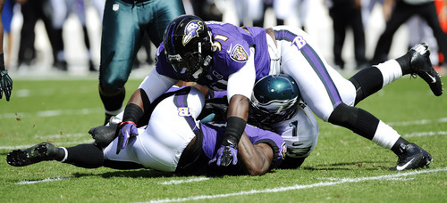 Philadelphia Eagles quarterback Michael Vick (7) is sacked by Baltimore Ravens strong safety Bernard Pollard, left, and linebacker Courtney Upshaw, top, in the first half of an NFL football game, Sunday, Sept. 16, 2012, in Philadelphia. (AP Photo/Michael Perez)